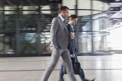 Corporate businessmen with coffee walking outside building - stock photo