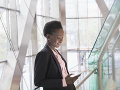 Corporate businesswoman using digital tablet in modern office lobby Stock Photos