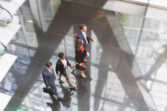 Corporate business people walking in modern office lobby - stock photo