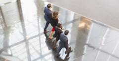 Corporate business people walking in a row in modern office lobby - stock photo