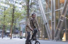 Corporate businessman riding bicycle outside modern building Stock Photos
