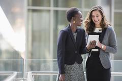 Smiling corporate businesswomen using digital tablet Kuvituskuvat