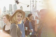 Portrait smiling young woman drinking beer at rooftop party - stock photo