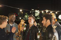 Young men drinking beer and talking at rooftop party Stock Photos