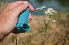 Hand with asthma aerosol in outdoor near flowers Stock Photos