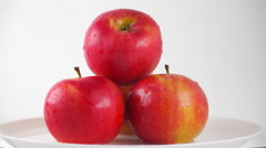 Red apples on plate and dripping water against white background. 4K ProRes dolly Stock Footage