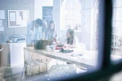Design team meeting at boardroom table in design studio - stock photo
