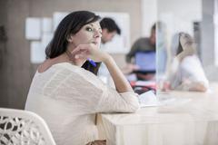 Female designer daydreaming at desk in design studio Stock Photos