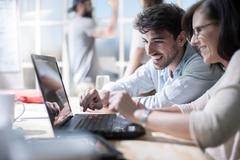 Male and female designers working together on laptop in design studio Stock Photos