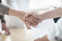 Close up of client and designer shaking hands in design studio - stock photo