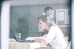 Window view of female designer working on laptop at design studio Stock Photos