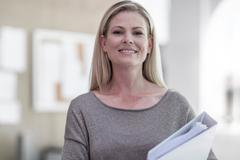 Portrait of female designer carrying file in design studio Stock Photos