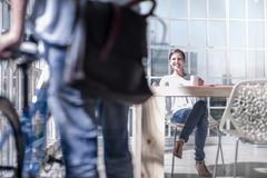 Female designer working on design studio patio talking to cycle courier - stock photo
