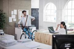 Male designer leaving work with bicycle in design studio - stock photo