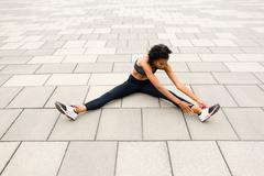 Woman sitting on pavement legs apart doing stretching exercises Stock Photos