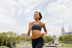 Woman wearing sports clothing jogging in city - stock photo