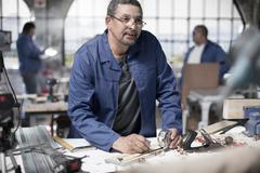 Carpenter measuring plank in workshop - stock photo