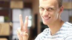 Young Designer in office showing victory sign, Successful Project Completion Stock Footage