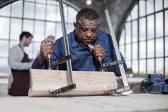 Carpenter gluing and clamping wood in workshop - stock photo