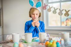 Boy at table wearing bunny ears decorating eggs for Easter - stock photo