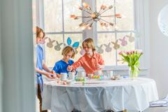 Boys at dining table decorating eggs for Easter Stock Photos