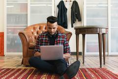 Man sitting on floor against armchair using laptop Stock Photos