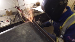 Close up steadicam shot of young man welding in a machine shop Stock Footage