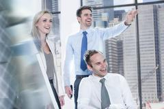 Businessmen and businesswoman laughing in office Kuvituskuvat