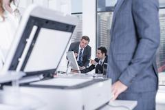 Businessman and businesswomen chatting by photocopier in office, colleagues Stock Photos