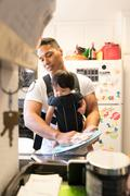 Father with baby in carrier, washing dishes - stock photo