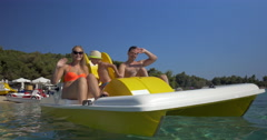 Happy family waving hands while sailing on pedal boat Stock Footage