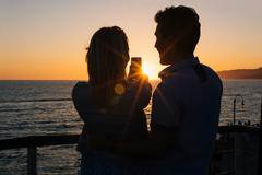 Silhouetted young couple taking smartphone selfie at sunset, Santa Monica, - stock photo