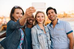 Adult friends taking smartphone selfie on pier, Santa Monica, California, USA Kuvituskuvat