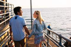 Rear view of young couple strolling on pier, Santa Monica, California, USA Kuvituskuvat