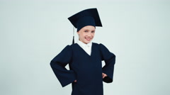 Portrait happy graduate girl 7-8 years in the mantle and hat has power Stock Footage