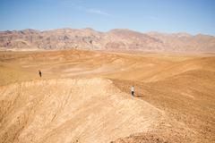 Man and boy exploring rim in desert, Olancha, California, USA - stock photo