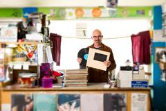 Portrait of mature man in record shop, putting record into record sleeve - stock photo
