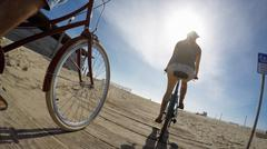 Low angle view of couple cycling on boardwalk at Venice Beach, California, USA - stock photo