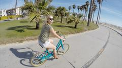 Portrait of young woman cycling at Venice Beach, California, USA - stock photo