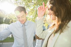 Embarrassed flirty young businesswoman and man on sunlit street - stock photo