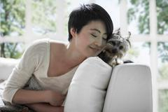 Woman snuggling up to pet dog on sofa - stock photo