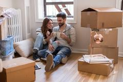 Moving house: Young couple sitting in room full of boxes, drinking hot drink Stock Photos