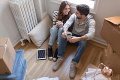 Moving house: Young couple sitting in room full of boxes, drinking hot drink - stock photo