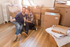 Moving house: Young couple sitting in room full of boxes, holding champagne - stock photo