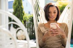 Young woman relaxing on garden hammock reading smartphone texts Stock Photos