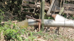 Farmer using pushcart to pump water out of fish pond Stock Footage