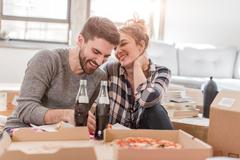 Moving house: Young couple eating pizza in new home, surrounded by boxes Stock Photos