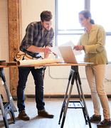 Carpenter and client at workbench discussing blueprint - stock photo