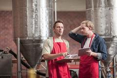 Colleagues in microbrewery holding clipboards and digital tablets - stock photo