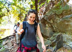 Young female and male hikers hiking by rocks in forest, Arcadia, California, USA - stock photo